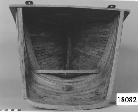 """Modell av fernissat trä visande akterstäv i tvärgående genomskärning utan bordläggning. Delarna är sammanfogade med spik och krampor av järn. Modellen är hängd på en fernissad plywoodskiva, sekundär montering. På skivan sitter en metallbricka med instansad text: """" AKTERSTÄV TILL SEGELFARTYG """". Plywoodskivan och metallbygeln är sekundära och ingår ej i föremålet."""