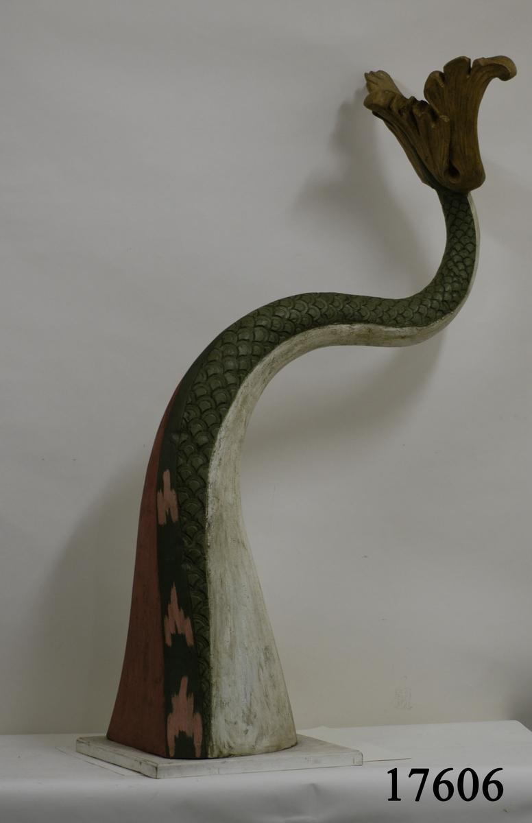 Draksvans gjuten i plast. Svansen gör en s-formad sväng med fenorna pekande uppåt. Målad och patinerad. Fjällen är olivgröna, baksidan vit, översidan röd och grön, fenorna ockragula. Svansen är fäst till en fyrkantig träplatta som är målad i vitt.