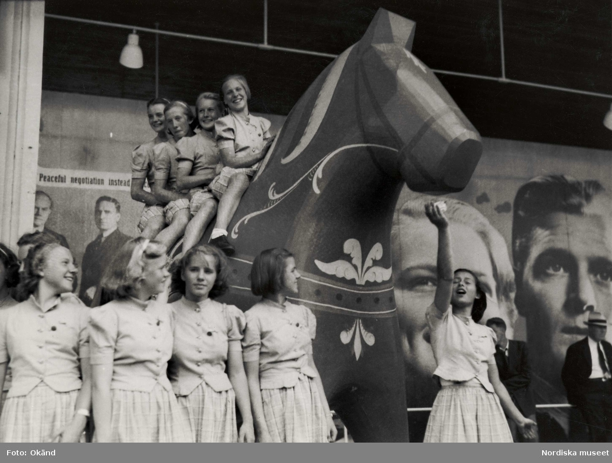 Fyra flickor sitter på en stor dalahäst vid svenska paviljongen på världsutställningen i New York 1939