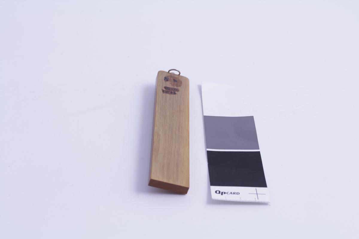 Termometer til innebruk. Består av plate i teak, med metallhempe til å henge på veggen. Glass med kvikksølvsøyle festet på messingplate som igjen er montert på teakplaten. Termometeret er av enkel utførelse. Gradeinndeling: 0-50 C