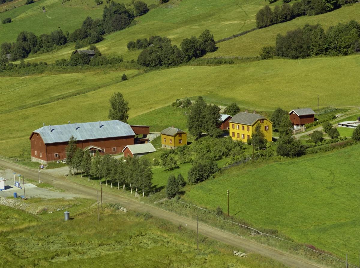 Tokstad. Gårdsbruk. Gul, stor hovedbygning,rød driftsbygning, mange små hus. Kulturlandskap