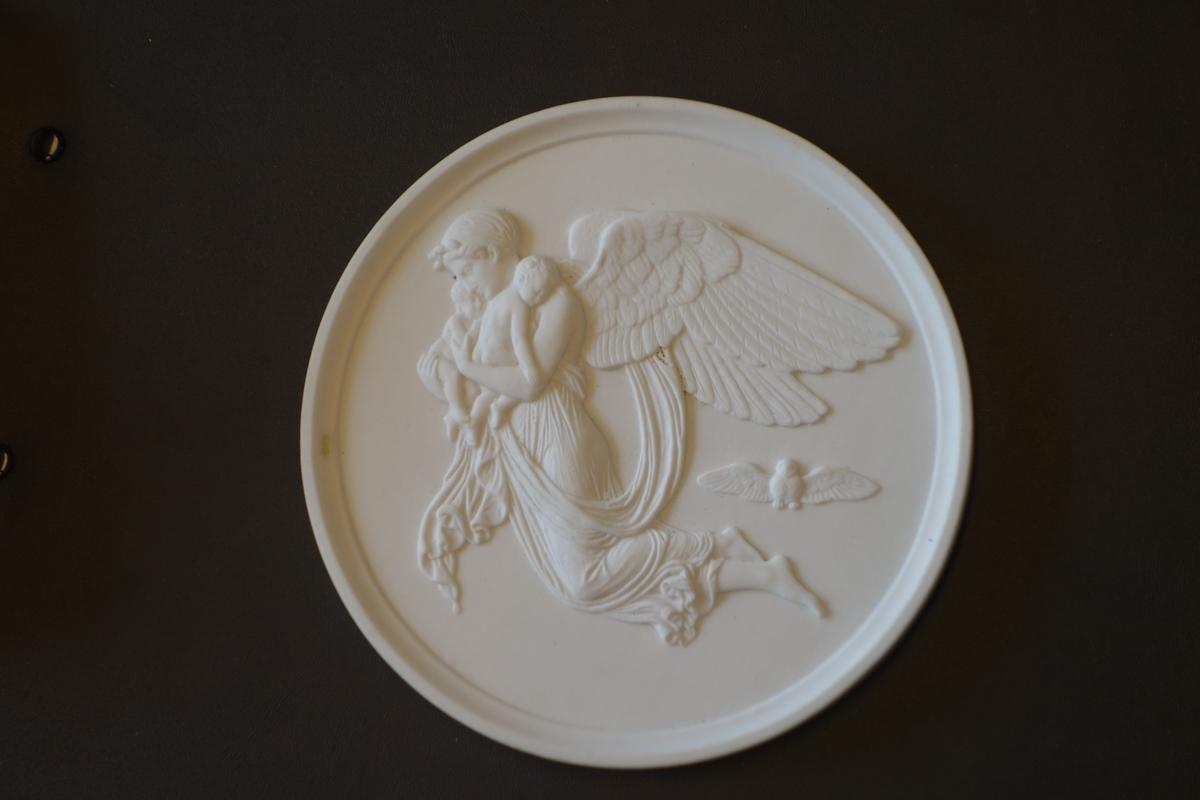 Rundt porselensrelieff med profilert kant. Motivet i relieffet er en bevinget kvinnefigur som svever med to barn i armene, mens en ugle flyr under vingene hennes.