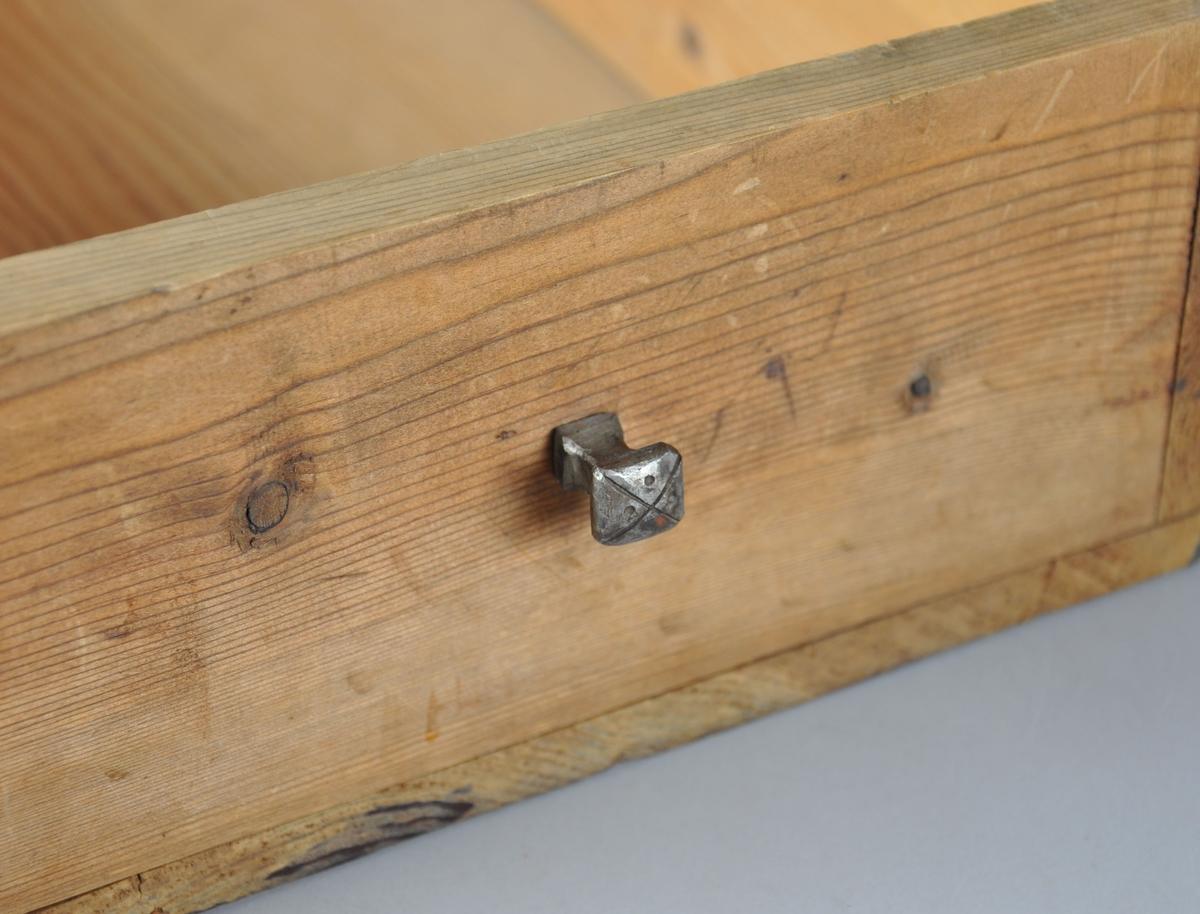 Rektangulær skuffe med metallknott på framsiden. Knotten har innrisset med et kryss med fire punkter. Skuffen hører sannsynligvis til et skap.