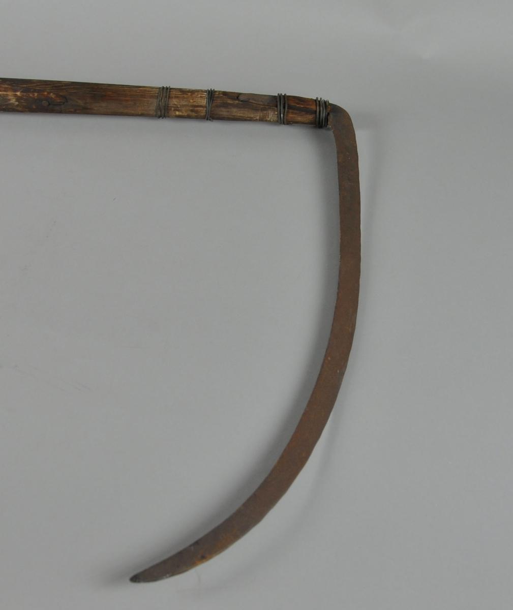 Ljå med blad. Orven har en kantete utforming og er lett innsvingt mellom håndtakene.  Øverste del på ljåen er dekorativt skåret, det samme gjelder øverste håndtak. Bladet er festet til orven med metalltråder.