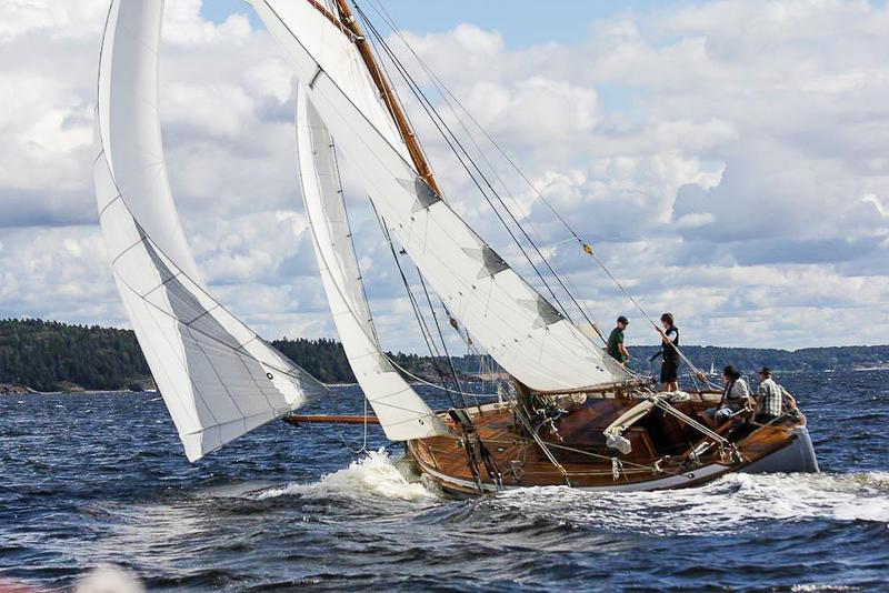 Skøyta S/Y Venus i vannet, tre seil, fire personer ombord. I bakgrunnen utsikt til skog. (Foto/Photo)
