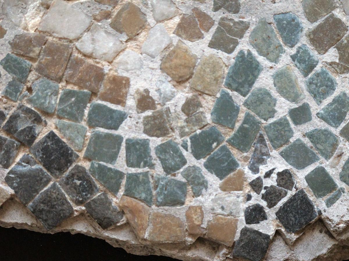 Mangefarget mosaikk fragment, tilnærmet rektangulært av form. Grønne, hvite, grå og gule tesseraer i naturstein, satt i fin kornet, hvit mørtel. Steinene av ulik størrelse, satt bueformede mønster.