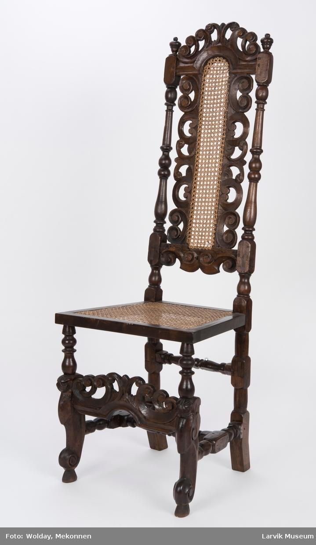 Form: Barokk, rett høy gjennombrutt rygg, dreide og høvlede bakstolper i ett med bakben, dreide og skårne forben, volutt nederst ,sprosseverk,