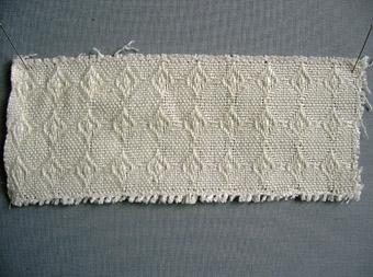 Vävprov i linne vävt i kypertbindning/kypertvariation, gåsögon?Varp och inslag i halvblekt/vitt lingarn.
