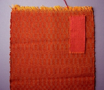 """Två vävprover, gåsögonmönstrade möbeltyger i bomull och ull. Två olika färgställningar; ett orangerött och ett rosarött. WLHF-0775:1 Varp i orange bomullsgarn nr 16/2.Inslag i rött 1-trådigt ullgarn; möbeltygsgarn. Två trådar tillsammans per inslag.Mått: 290 mm, 350 mm. WLHF-0775:2 Varp i orange bomullsgarn nr 16/2.Inslag i ljusrött 1-trådigt ullgarn; möbeltygsgarn. Två trådar tillsammans per inslag. Mått: 53 mm, 127 mm.WLHF-0775:2 liknar WLHF-0559 som vävdes för Gästis 1991 till stolarna i restaurangen. Foto på stolar (2007 ngt blekta) samt scannat tidningsurklipp finns i datamapp """"Tillbehör"""". Solvnota finns."""