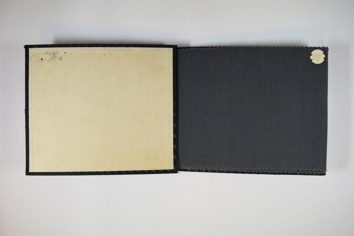 Prøvebok med 6 stoffprøver. Middels tykke stoff med skrå striper i vevmønsteret. Kyperbinding/diagonalvevd. Stoffene ligger brettet dobbelt i boken slik at vranga dekkes. Stoffene er merket med en rund papirlapp, festet til stoffet med metallstift, hvor nummer er påført for hånd. Innskriften på innsiden av forsideomslaget indikerer at alle stoffene i boken har kvalitetsnummer 148B.   Stoff nr.: 148B/1, 148B/2, 148B/3, 148B/4, 148B/5, 148B/6.
