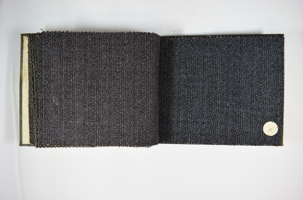 Prøvebok med 6 stoffprøver. Middels tykke stoff med mønster. Stoffene ligger brettet dobbelt i boken slik at vranga dekkes. Stoffene er merket med en rund papirlapp, festet til stoffet med metallstift, hvor nummer er påført for hånd. Innskriften på innsiden av forsideomslaget indikerer at alle stoffene har kvalitetsnummer 105.   Stoff nr.: 105/25, 105/26, 105/27, 105/28, 105/29, 105/30.