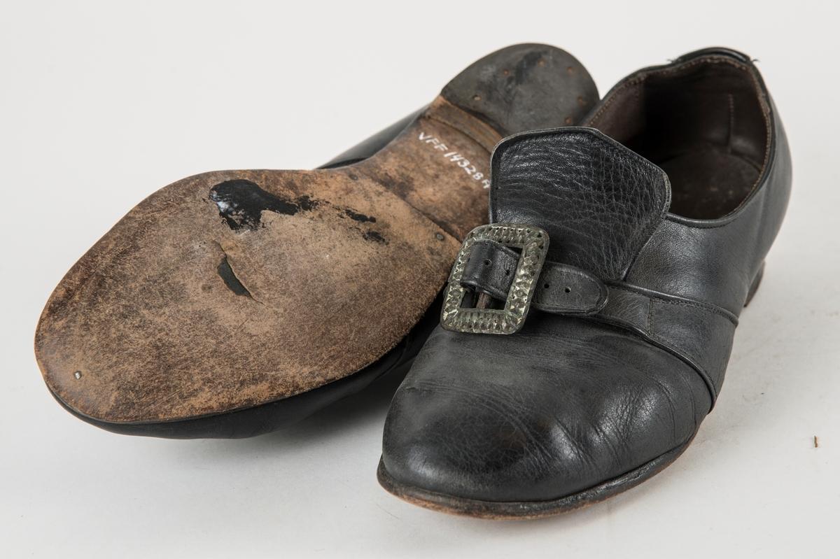 Sko i skinn med pløse utanpå. Reim over foten til å feste tinnspenne i. Fóra med skinn.