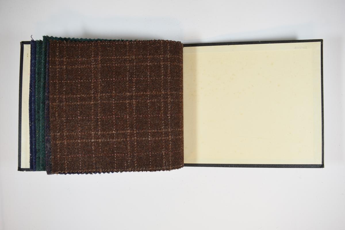 Prøvebok med 3 stoffprøver. Middels tykke stoff med diskret rutemønster. Stoffene ligger brettet dobbelt i boken. Stoffene er merket med en rund papirlapp, festet til stoffet med metallstifter, hvor nummer er påført for hånd. Innskriften på innsiden av forsideomslaget indikerer at alle stoffene har kvaliteten 167B.   Stoff nr.: 167B/34, 167B/35, 167B/36, 167B/37, 167B/38, 167B/39.