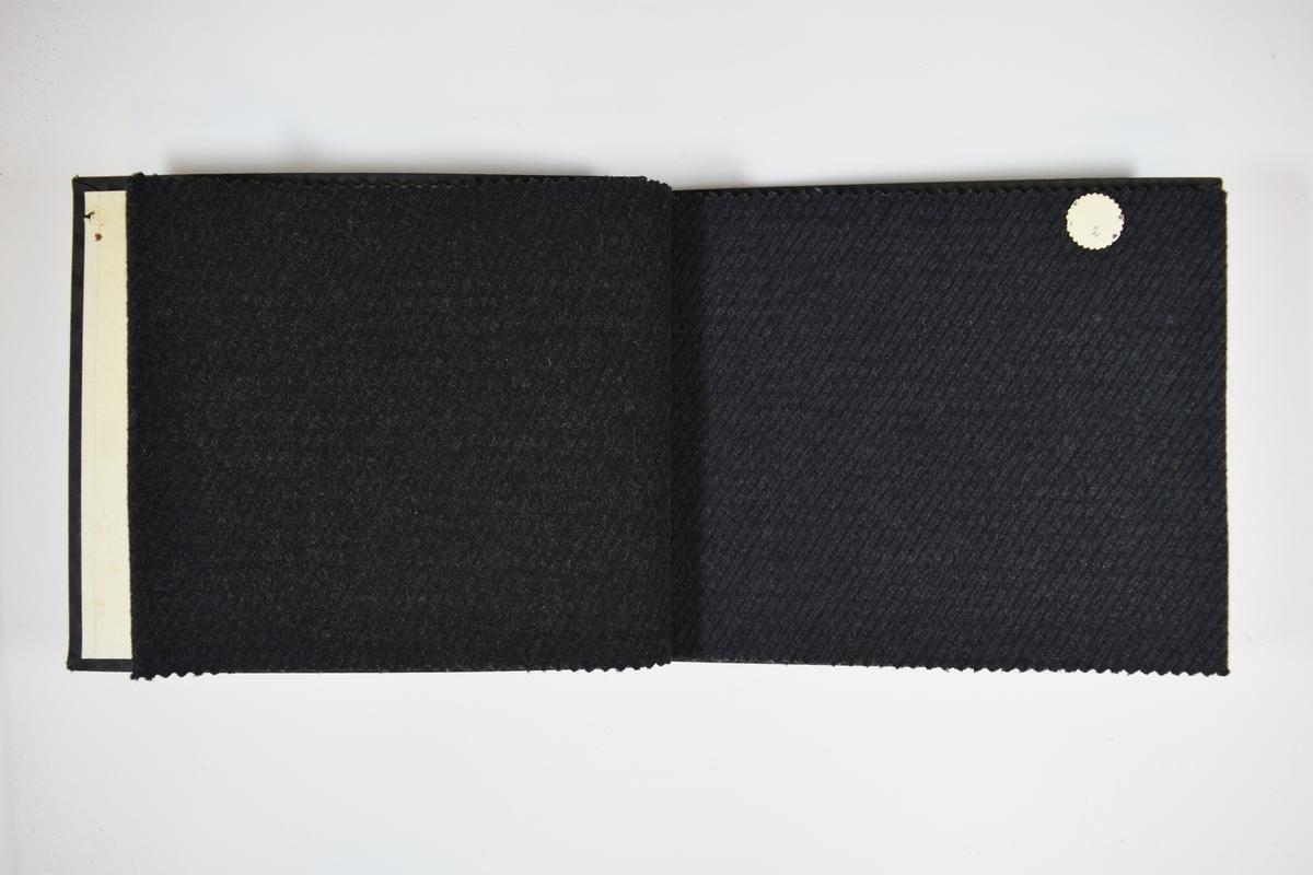 Prøvebok med 3 stoffprøver. Middels tykke stoff med skrå striper. Stoffene ligger brettet dobbelt slik at vranga skjules. Stoffene er merket med en rund papirlapp, festet til stoffet med metallstifter, hvor nummer er påført for hånd. Innskriften på det første stoffet indikerer at alle stoffene har kvalitetsnummer 202.   Stoff nr.: 202/1, 202/2, 202/3.