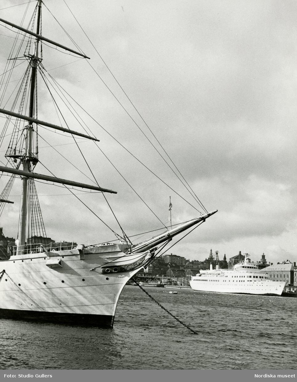 Vy över Slussen och Södermalm, Stockholm. I förgrunden segelfartyget HMS af Chapman. I bakgrunden passagerarfartyget M/S Ilmatar som ligger förtörjt vid Skeppsbrokajen.
