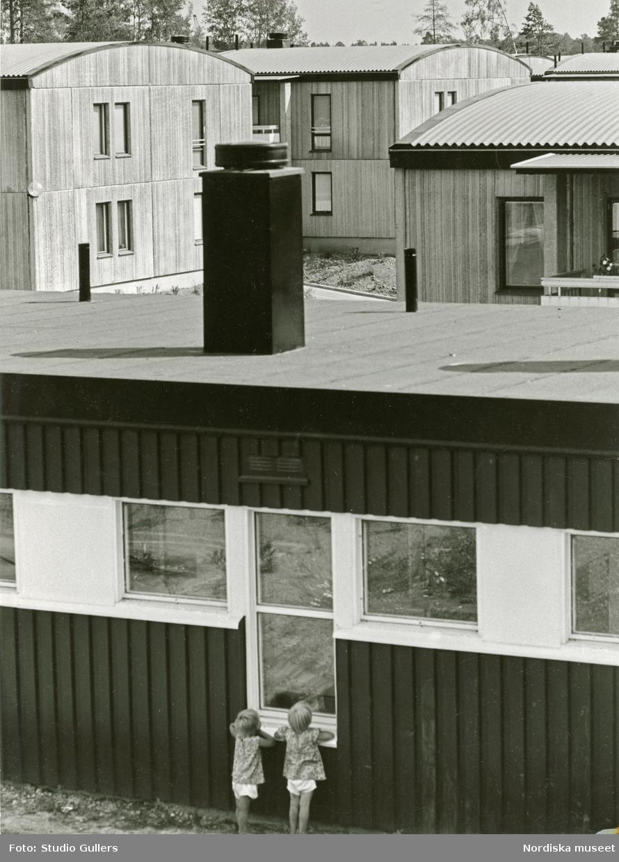 Vy över villabebyggelse. I förgrunden två barn som tittar in genom ett fönster.