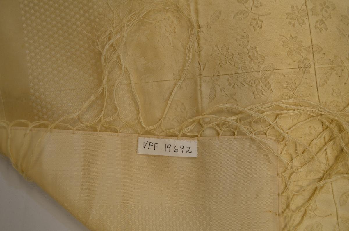 Tørkle i beige silkedamask med lysebrune rosebordar langst kantane. Påsette frynser i beige 10,5 cm lange.