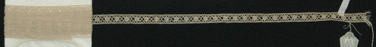 Vadstenaspets Mellanspets, 285 x 1,4 cm. Obl. lintråd. Vävbottensrutor och varierade brabanthål. Efter mönster från Nordiska museet. Vadstena knyppelskolor nr 882.  Katalogiserad av Karin Nordenfelt, Elisabet Stavenow, Marie-Louise Wulfcrona-Dagel.