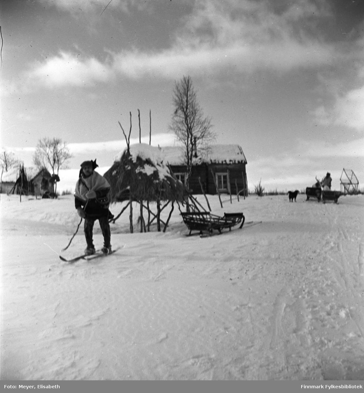 Vinterhus til reindriftssamer. Same på ski med bjørkekjepp som stav. I bakgrunnen sees en slede, et vinterlager og flere hus. Til høyre i bildet sees en same med slede og en hund ved siden av. Bildet er tatt i 1939-40.