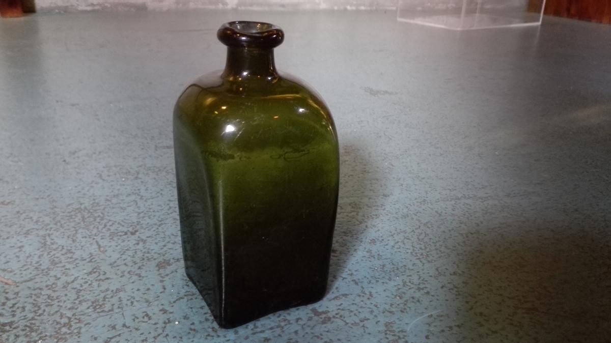 1 gammel flaske.  Firkantet flaske av mørk grønlig glass, kort hals med ring om mundingen.  Størrelsen i bunden 5,1 x 5,1 cm, høide 12,3 cm. Gave fra Roar Seltun, Lærdal.