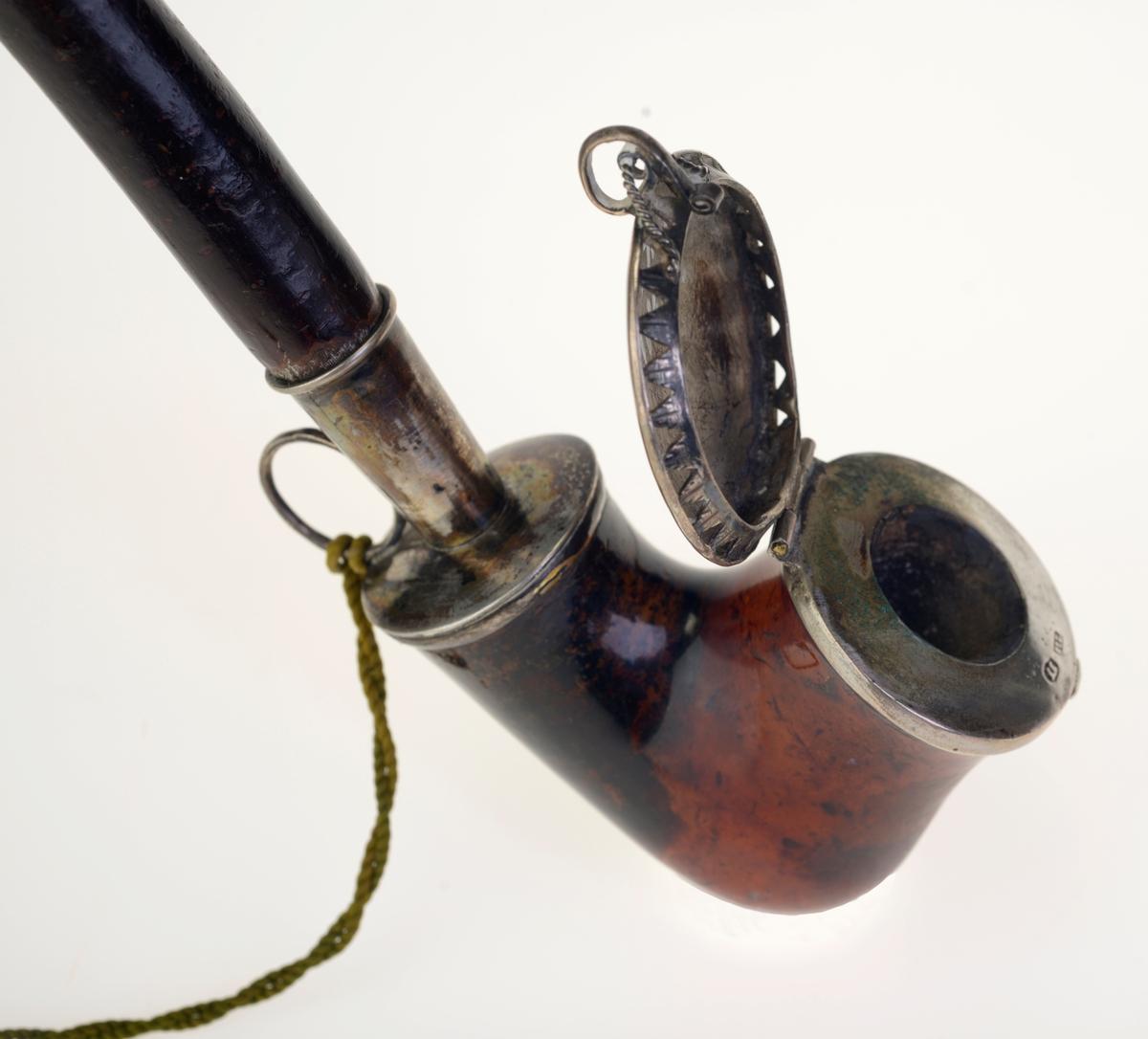 Langpipe med pipehode, piperør og halvparten av munnstykket. Pipehodet er laget av merskum og er brun/brunrød og svart på farge. Pipehodet har sølvlokk med fjærlås og i låsen er det festet en tvunnet snor av sølv. Langs kanten på lokket er det små luftehull formet som trekanter. Lokket er festet med hengsler. Festet til piperøret er også laget av sølv, og i bakkant er det en ring som fungerer som snorfeste. Det ene stempelet 11L betyr at sølvinnholdet er på 687 promille. Piperøret er laget av tre som har barken på, og det er brunsvart på farge. Munnstykket er trolig laghet av ibenholt og har enkle utskjæringer og en mansjett. Siste del av munnstykket mangler. Det er festet en grønn silkesnor med dusker i munnstykket og ringen på pipehodet.
