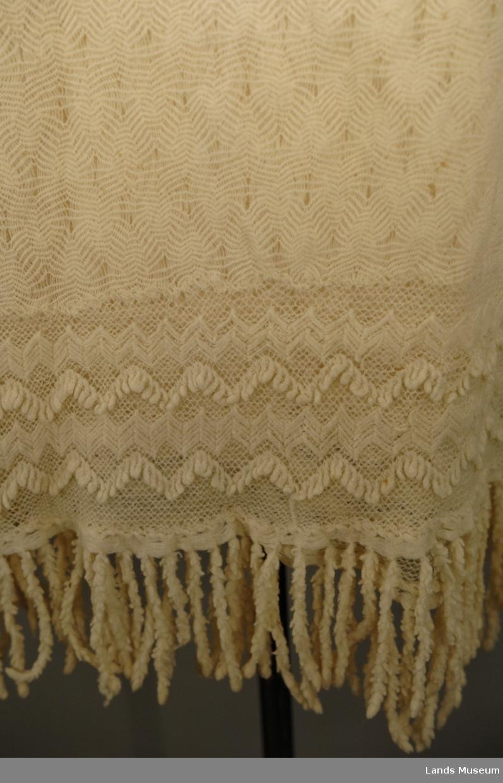 Strikket i tynn ulltråd. Den innerste firkanten er strikket i eit stykke. Knaten rundt påsydd slik at hjørnsne blir avrunda. Dersetter er det påsydd frynser med symaskin.