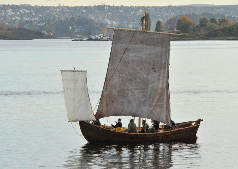 Trebåten Vaaghals på vannet med to seil, minst seks personer ombord, land i bakgrunnen. (Foto/Photo)