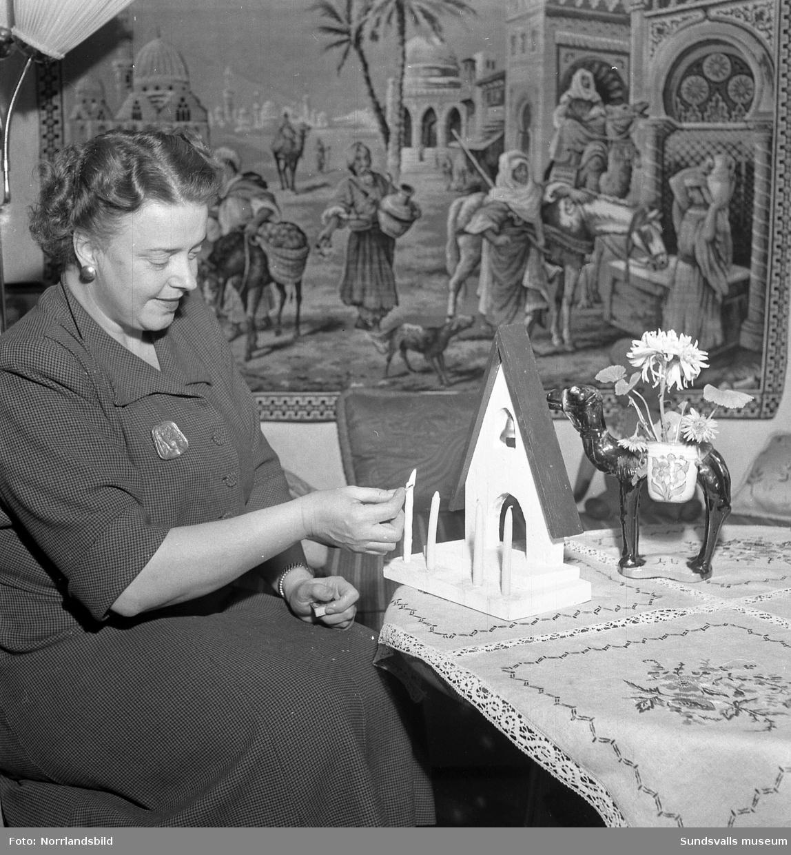 En kvinna tänder det första ljuset i adventsljusstaken.