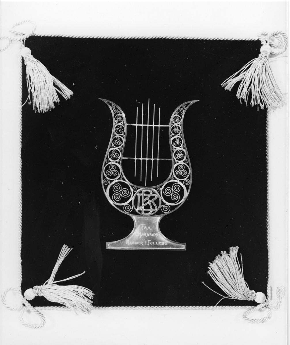 Lyre i sølv sydd fast på svart fløyelspute kantet med snorer og dusker i hjørnene. Initialene BB er utformet i jugendstil.