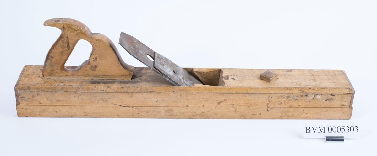 """Høvel i tre med horn/håndtak med dobbelt høveljern, uten kile. Jernet er produsert av """"ERIK ANTON BERG, ESKILSTUNA, GARANTI"""". På det minste står det i tillegg """"GULDMEDALJER Paris 1900, Stockholm 1897 f""""r b""""sta behandling af svenskt stål"""". To steder på hver langside og en gang på toppen er det brent inn """"SV"""". Langhøvel med stillingsknapp. Håndtaket er utformet som håndtaket på ei sag."""