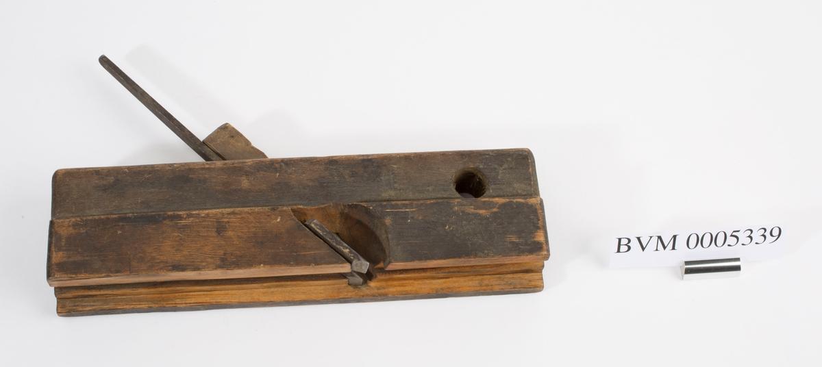 Fjærhøvel i tre med kile og høveljern. Styrekant på venstre langside. Gjennomgående hull i front på høvelstokken.