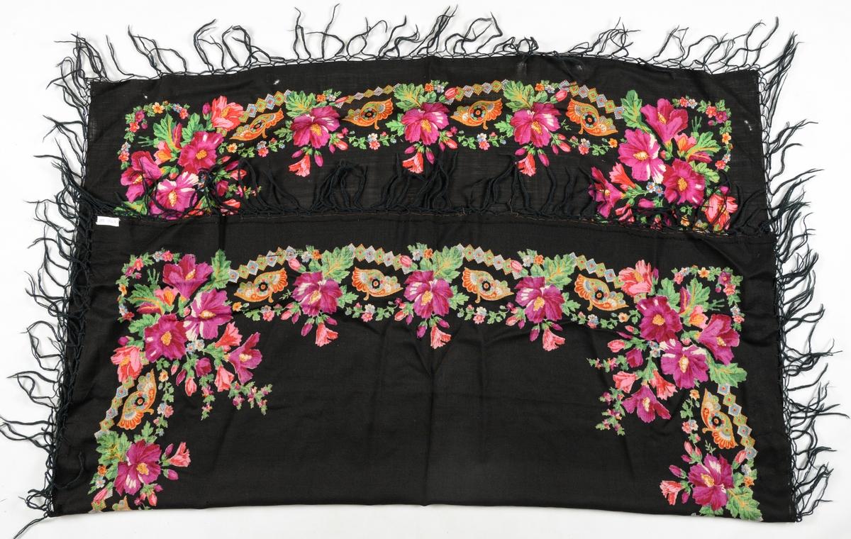 Sjal i svart ullmusseli med trykt blomsterbord langs sidene. Påsydde svarte ullfrynser.