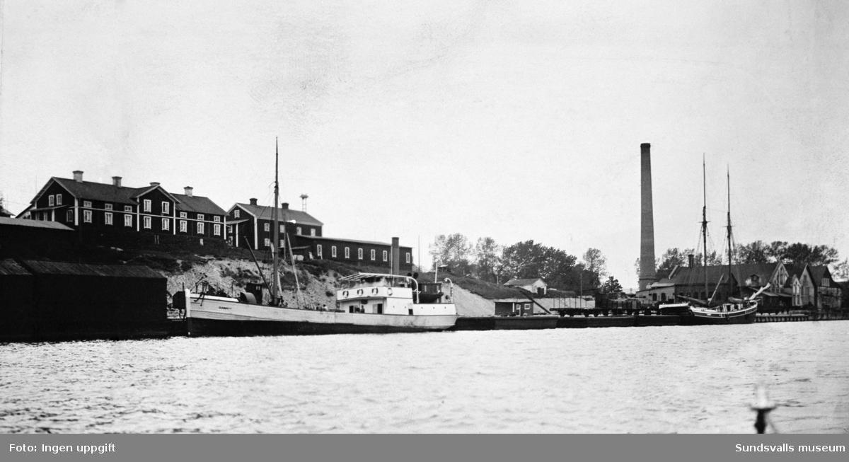 """""""Juni 1928. Nya Mokajen har tagits i bruk"""" Foto ur Hamnstyrelsens arkiv. """"Mons sågverk är nedlagt men byggnaderna och skorstenen är kvar. arbetarbostäderna, bl a """"Häktet"""" med sin vällingklocka, syns uppe på höjden helt nära stranden."""""""