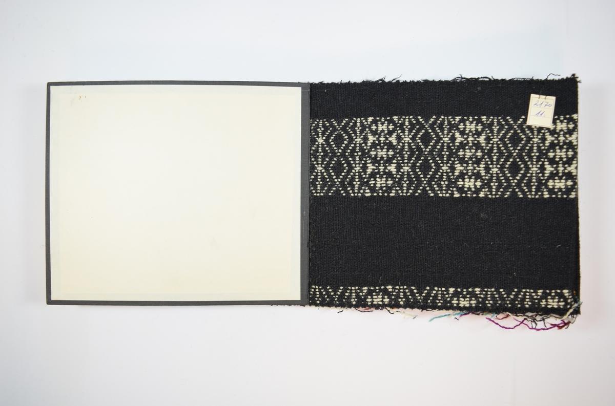 Rektangulær prøvebok med åtte stoffprøver og harde permer. Permene er laget av hard kartong og er trukket med sort tynn tekstil. Boken inneholder middels tykke, tette tofargede stoff med tykke striper av variert mønster. Mønsteret og bunnfargen (svart) er det samme for alle prøvene i boken, men dekorfargen varierer mellom stoffene. Stoffene er merket med en firkantet papirlapp, festet til stoffet med metallstifter, hvor nummer er påført for hånd.   Stoff nr.: 2170/11, 2170/12, 2170/13, 2170/14, 2170/15, 2170/16, 2170/17, 1270/18.