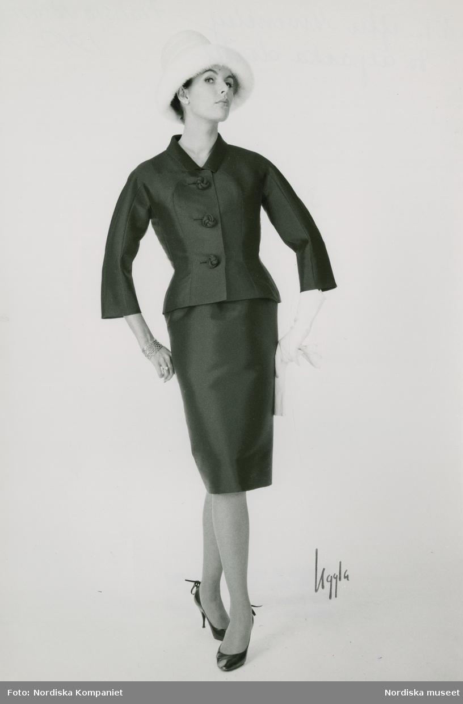 Modell i svart alpackadräkt, mösshatt, handskar, armband och pumps. NK:s Franska efter Givenchy, höst.