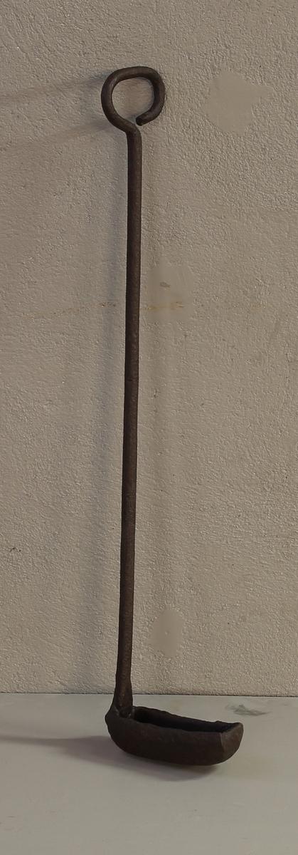 Øsekar med skaft og håndtak. Øsekaret er rektangulær i formen og skaftet avlangt og sylinderformet. Avsluttes med et sirkelformet håndtak.