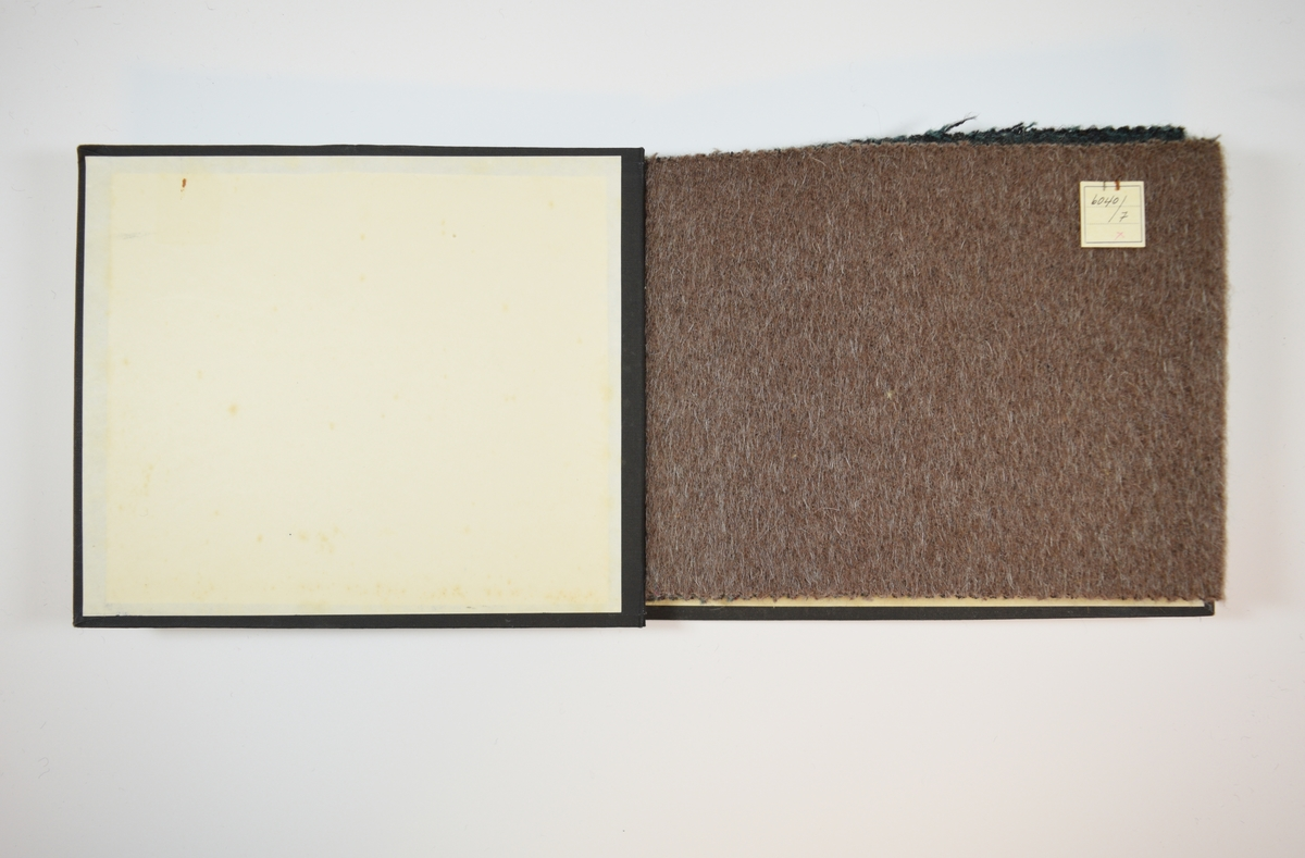 Rektangulær prøvebok med harde permer og fem stoffprøver. Permene er laget av hard kartong og er trukket med sort tynn tekstil. Boken inneholder tykke melerte ullstoff, det siste med striper. Stoffene ligger brettet dobbelt i boken slik at vranga skjules. Vevmønsteret er noe mer synlig på vranga, der er sorte tråder også synlige, noe som ikke syns fra forsiden. Stoffene er merket med en firkantet papirlapp, festet til stoffet med metallstifter, hvor nummer er påført for hånd.   Stoff nr. 6040/7, 6040/8, 6040/9, 6040/10, 6040/11.