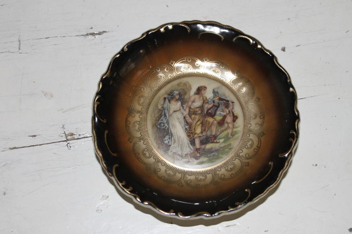 Prydnadsskål i porslin från Bavaria. Rund med motiv i mitten. Förgyllda detaljer runt motiv och runt kant. Svart och brun ovansida.