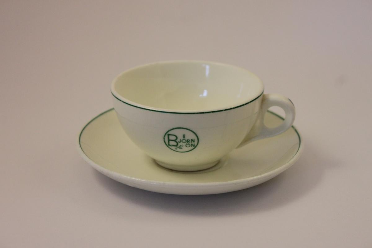 Kaffekopp och fat i benporslin märkta med Björnön i en ring och med en kvist i grönt på ena sidan av koppen. Gröna ränder runt koppen och fatets kant.
