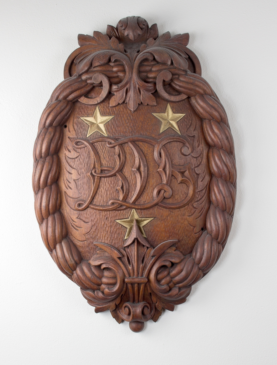 Ovalt emblem utført i tre med bokstavene BDS i senter, omkranset med tre stjerner og tau.