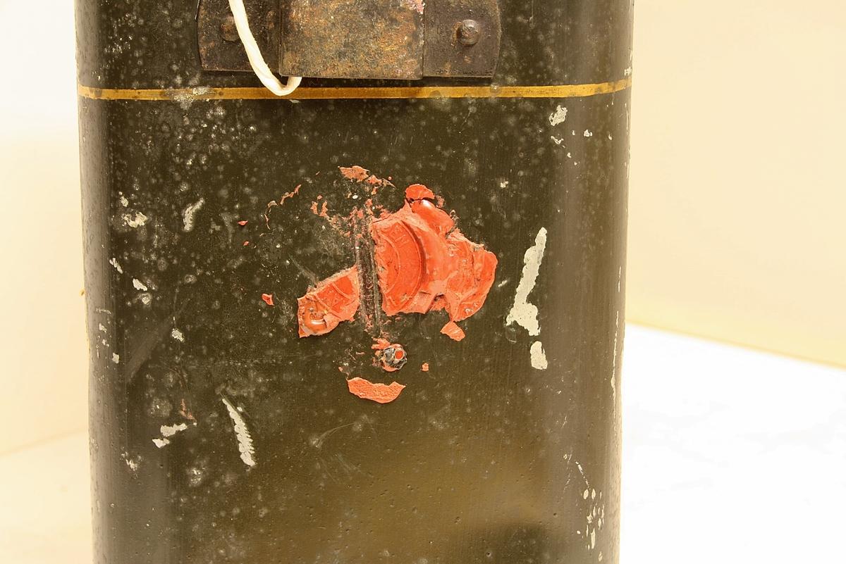 Avrundet, rektangulær boks. Den norske løve på fronten. Rester etter rødt segl. Hvit snor i plast.