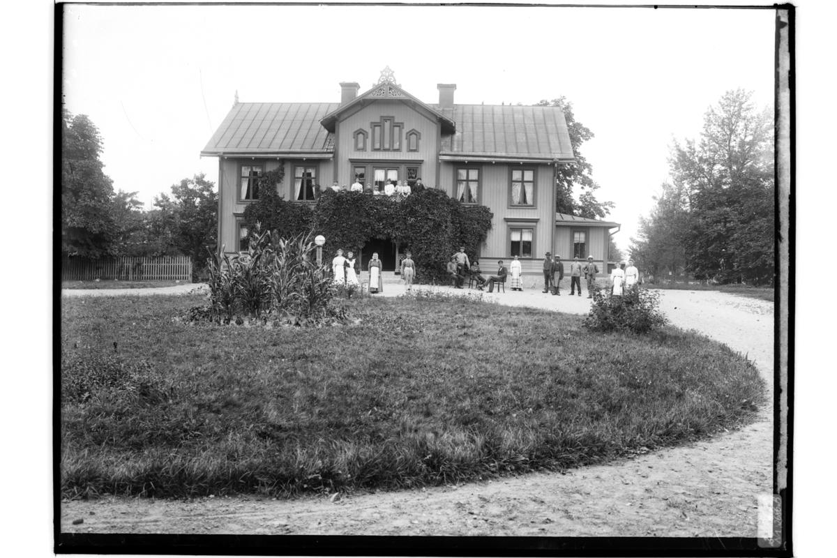 Rättaren Robert PetterssonTvåvånings bostadshus med frontespis och balkong. 24 personer framför huset och på balkongen.