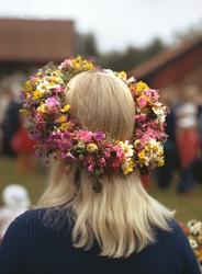 Midsommar. Flicka med blomsterkrans i håret porträtterad bak