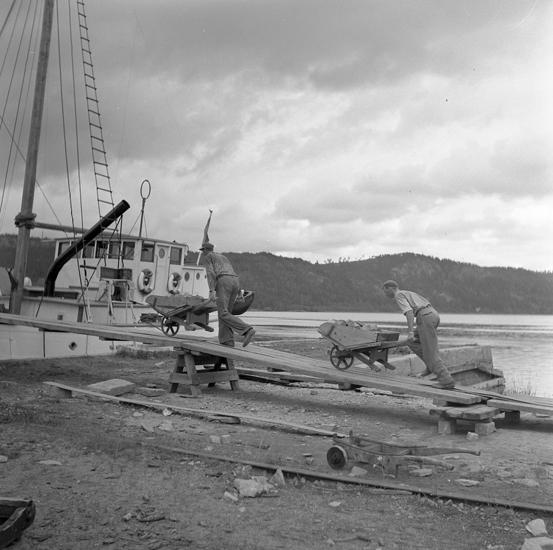 ::Arbetare som kör sten i skottkärror, och lastar en båt.