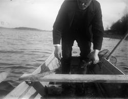 August Alinder vittjar en ryssja i båten, Altuna socken, Upp