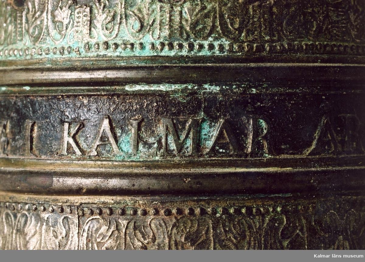 KLM 18217. Vällingklocka. Av malm. Dekor med gjutna lister samt text: GJUTEN AF I.P. FORSBERG I KALMAR ÅR 1857 samt ERIC SWARSS. Klockan är monterad på en metallstång, denna är målad i grå färg, som rostskydd, under senare tid.