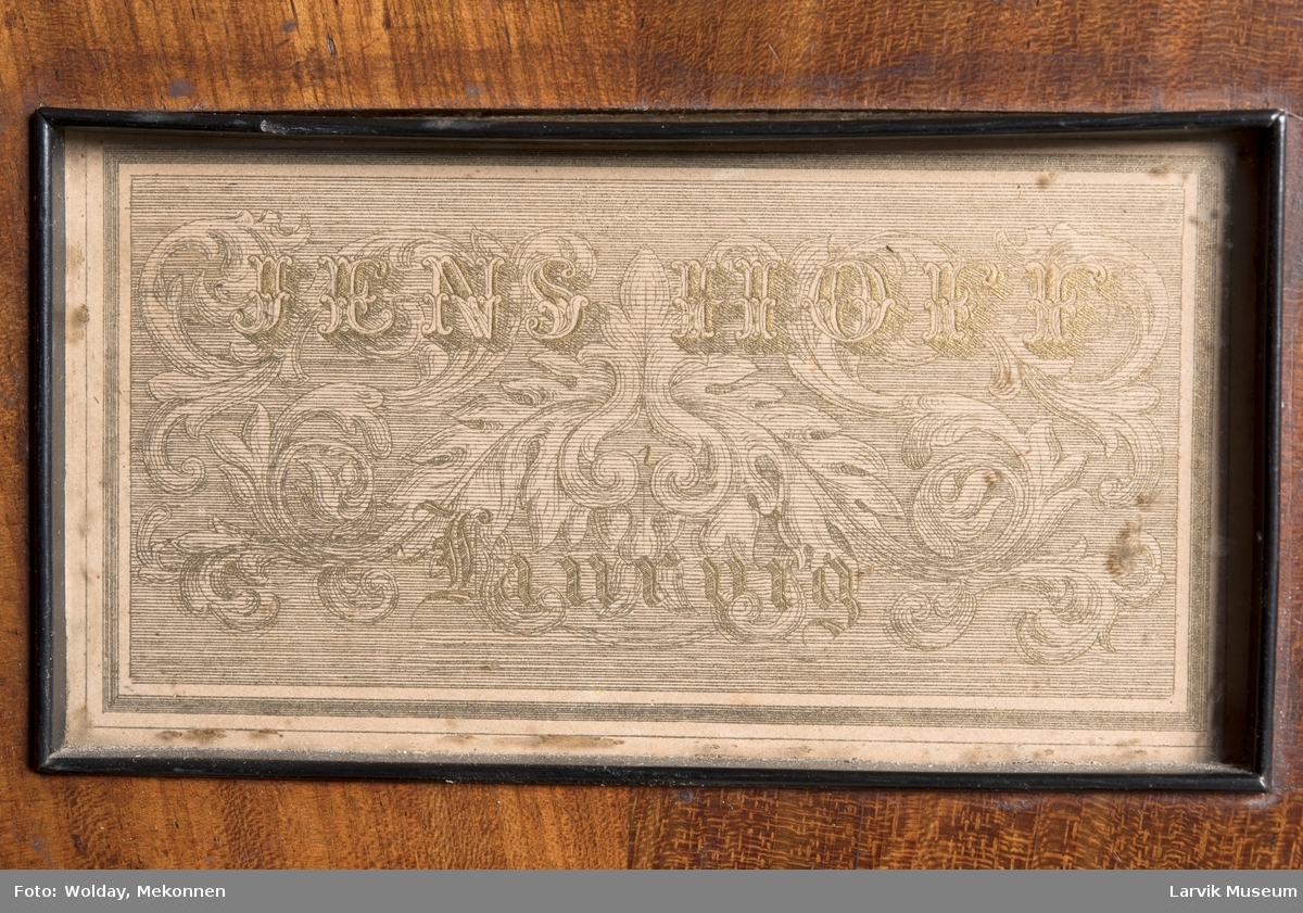 Rektangulært, stekt svugne ben tilnærmet. c-form korte bindn. under lokkplate med glass hvor signert Jens Hoff, Laurvig en pedal festet til pedalfot(?)