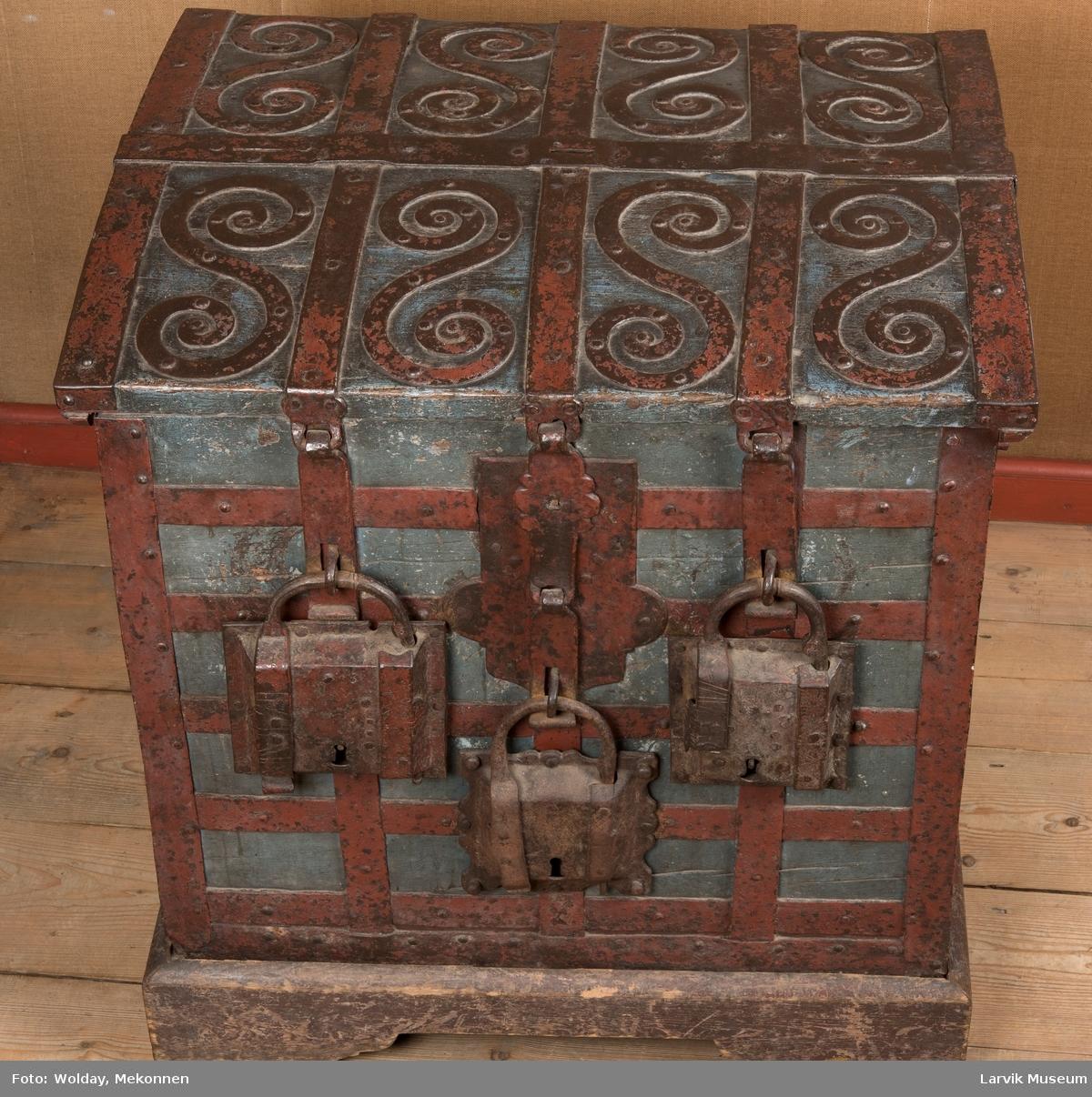 Kiste med buet lokk, beslått med rette, krysslagte  jernbånd. 8 dobbeltspiraler av jern på oversiden av kistelokket. 1 lås og 3 hengelåser på ene siden. 1 håndtak på hver kortside.