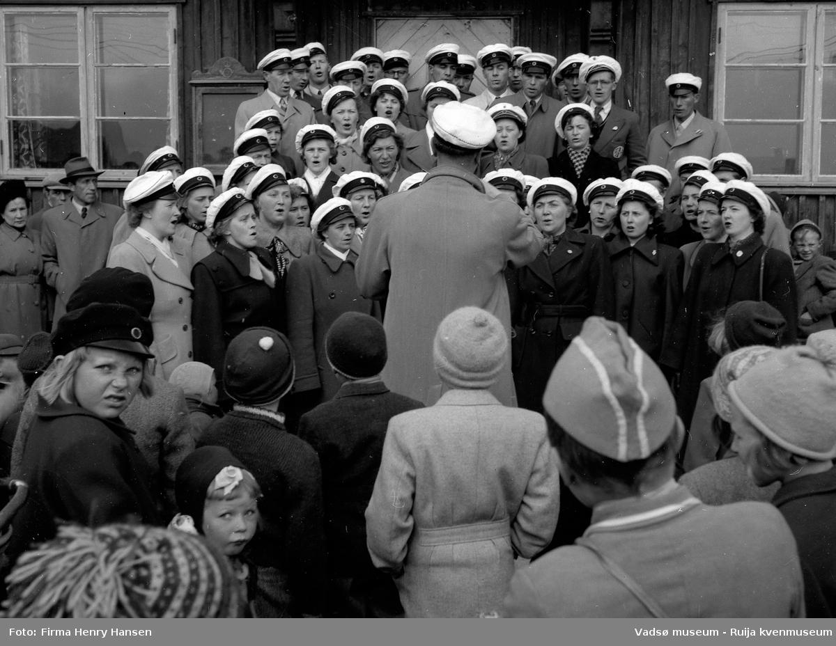 Vadsø sentrum 17. mai 1951. Korsangere foran postbrakka. Barn og voksne er tilskuere.