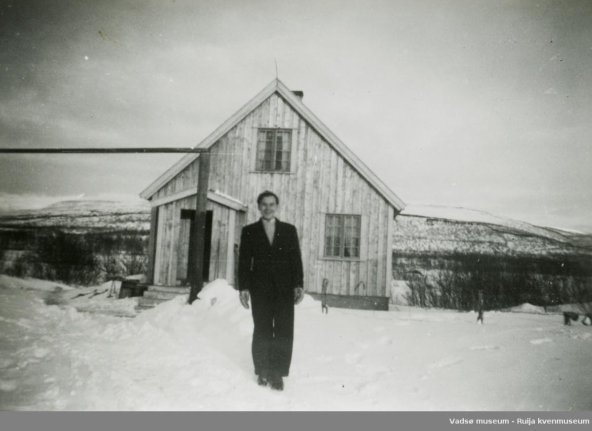 Mann foran et gjenreisingshus vinterstid. Antatt sted Vestre Jakobselv, ca. 1948.